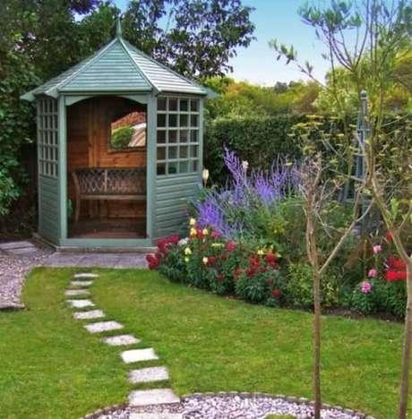 17. A estrutura em madeira com banco foi utilizada como enfeite de jardim nesse espaço. Fonte: Pinterest