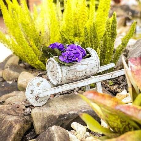 16. Invista em enfeites para jardim em tamanho miniatura como esse carrinho de mão barril. Fonte: Carro de Mola