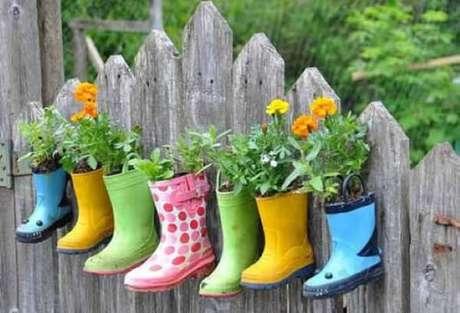 74. Enfeites para jardim feitos com botas fixadas na parede de madeira. Fonte: Pinterest