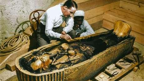 Arqueólogo britânico Howard Carter e um trabalhador egípcio examinam um caixão feito de ouro maciço dentro da tumba