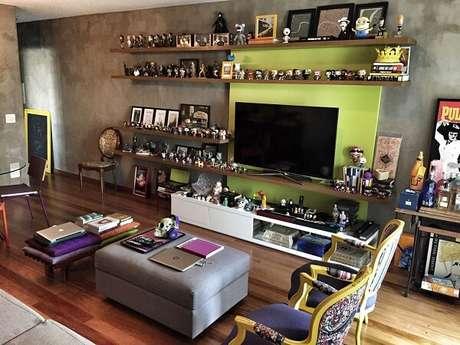 13. Estante para coleção e poltronas para sala de tv alegram o ambiente. Projeto por Tasselli Barros Arquitetura e Interiores