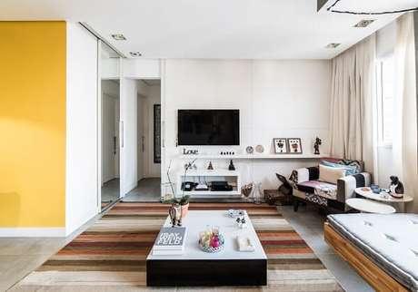 16. Móveis claros, tapete listrado e poltronas para sala de tv. Projeto por Pietro Terlizzi