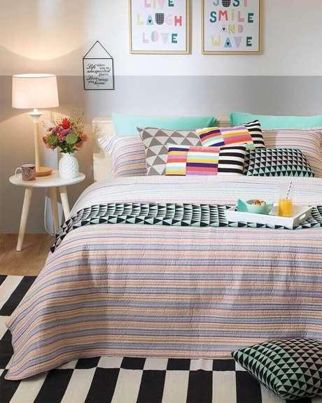 19. Mesa lateral de apoio para quarto decorado com parede pintada em duas cores e almofadas coloridas – Foto: Tok & Stok