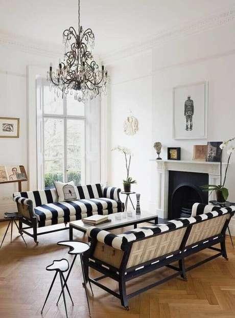 48. Aqui a sala com lustre candelabro e sofá listrado preto e branco foi decorada com duas mesa lateral de apoio com design diferente – Foto: Pinterest