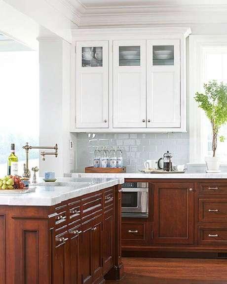 17. O armário de cozinha de madeira escura com tampo de granito branco encanta a decoração. Fonte: Pinterest