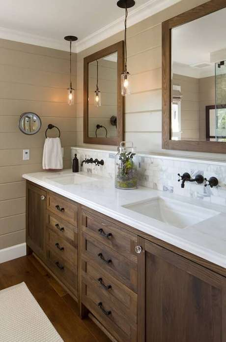 8. Armário de banheiro de madeira escura destaca a bancada com granito branco. Fonte: Home BNC