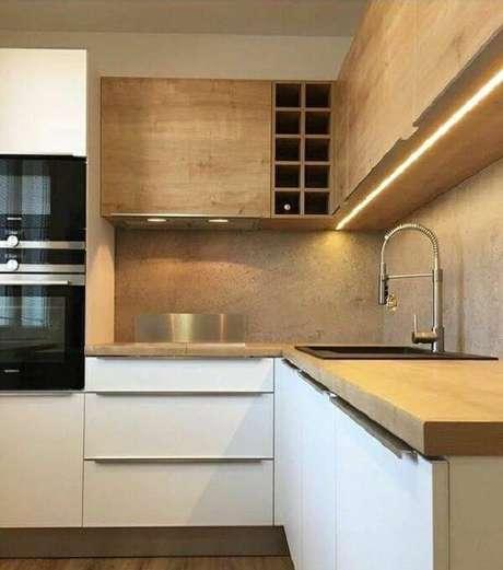 7. O armário de madeira para cozinha foi feito com marcenaria clara e iluminação embutida. Fonte: Revista Viva Decora