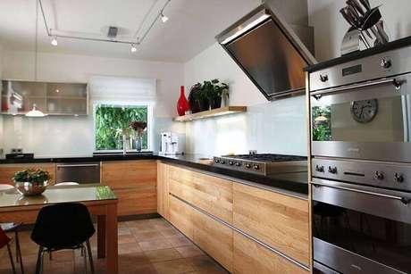 6. O armário de madeira para cozinha se mistura com equipamentos em aço inox. Fonte: Residence Style