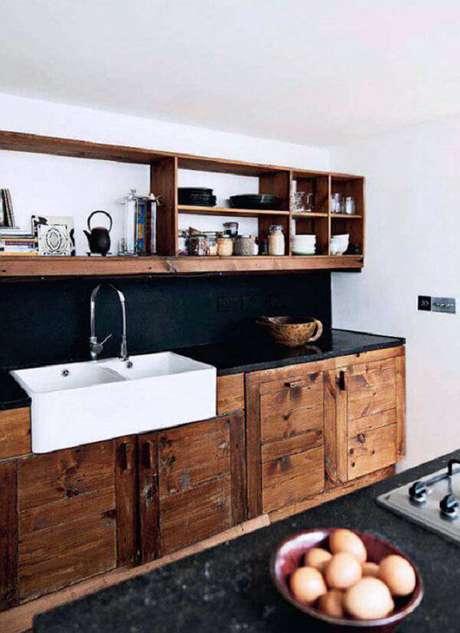 4. Armário de madeira maciça e bancada de granito preto complementam a decoração da cozinha. Fonte: Residence Style
