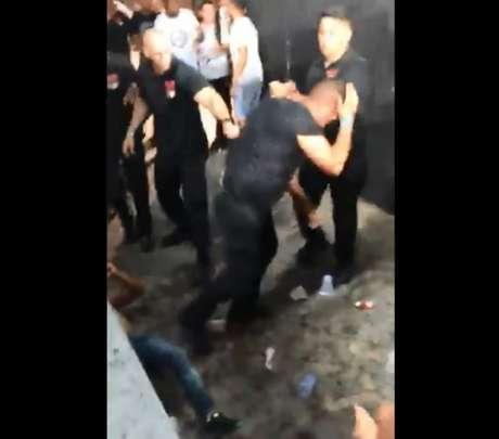 Segurança põe a mão na cabeça após ser agredido (Foto: reprodução)