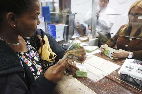 Mulher troca bolívares por dólares em casa de câmbio em Caracas 24/02/2015 REUTERS/Carlos Garcia Rawlins