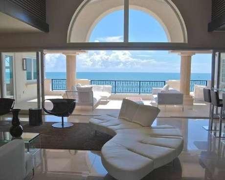 11. Sala com varanda ampla decorada toda branca com sofá sem braço branco moderno – Foto: HappyModern