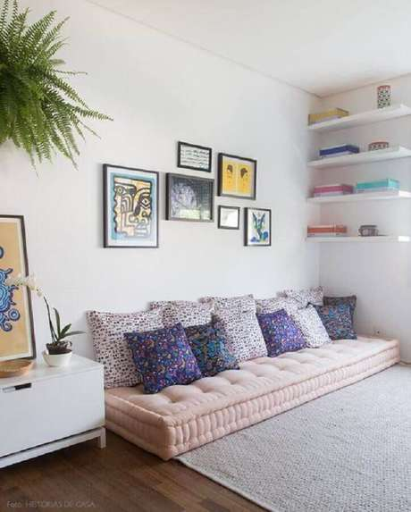 19. Decoração simples para sala com prateleiras brancas e sofá sem braço com várias almofadas – Foto: Histórias de Casa