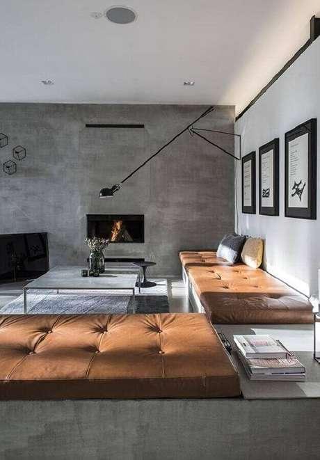 24. Decoração com estilo industrial para sala com parede de cimento queimado e sofá sem braço com acabamento em couro marrom – Foto: HappyModern