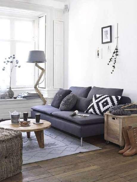 25. Sala pequena decorada com sofá 2 lugares sem braço e mesa de centro de madeira redonda – Foto: Simples Decoração