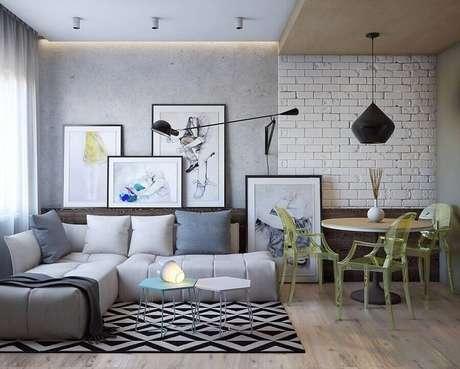 26. Sala decorada com parede de cimento queimado e sofá de canto sem braço – Foto: Reciclar e Decorar