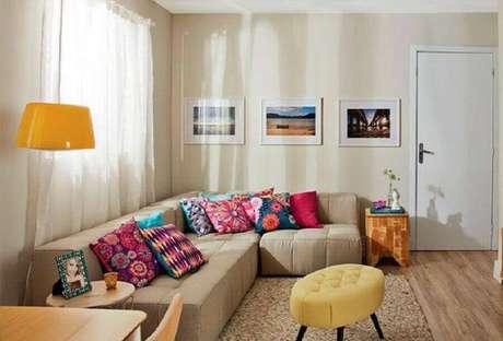 30. Sala decorada em tons neutros com sofá de canto sem braço e almofadas coloridas – Foto: Fala Moda