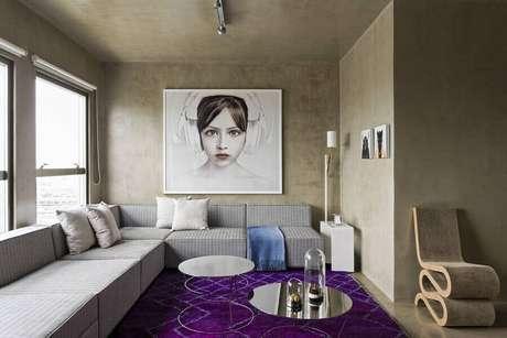 33. Sala moderna decorada com parede de cimento queimado e sofá sem branco de canto grande – Foto: Archello