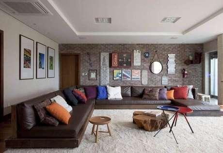 40. Sala ampla decorada com sofá de canto sem braço de couro – Foto: Juliana Pippi