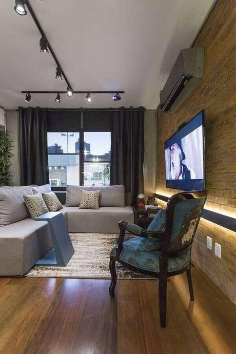 55. Sofá sem braço para decoração de sala com trilho de luz e parede de tijolinho à vista – Foto: Casa de Valentina