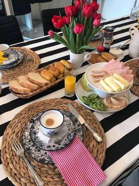 35. Mesa de café da manhã simples decorada com arranjo de tulipas vermelhas e toalha listrada preta e branca – Foto: Lar Doce Casa