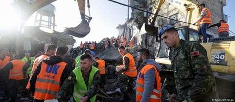 Equipes de resgate trabalham em busca de vítimas em escombros na cidade de Thumane