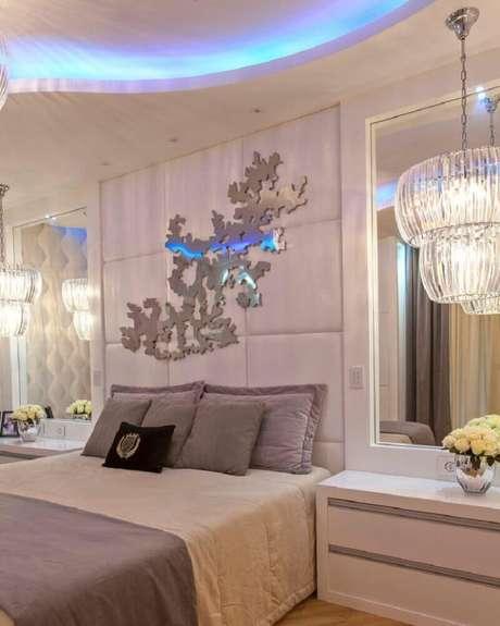15. Decoração com espelho para quarto e luminária sofisticada ao lado da cama