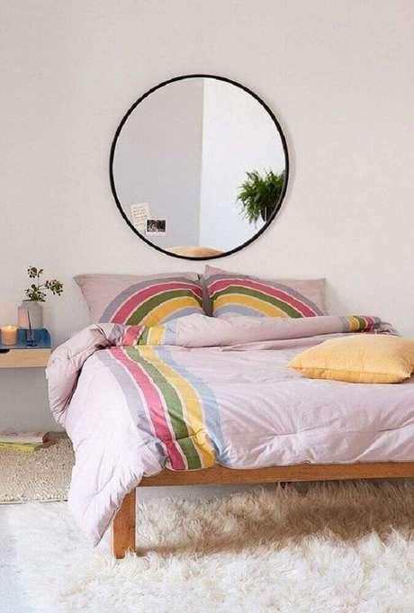 21. Modelo redondo de espelho para quarto decorando a cabeceira da cama