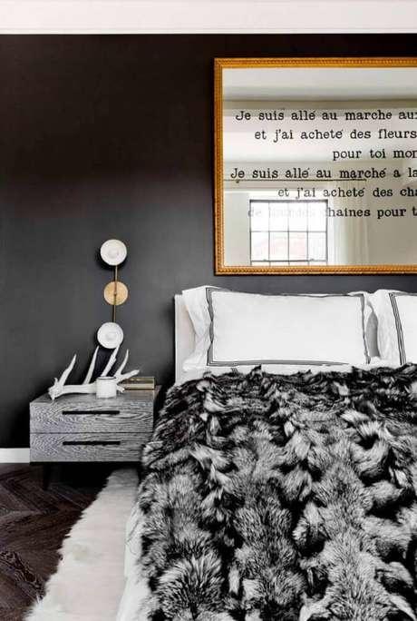 33. Decoração de quarto preto com espelho para quarto sobre a cabeceira com moldura dourada