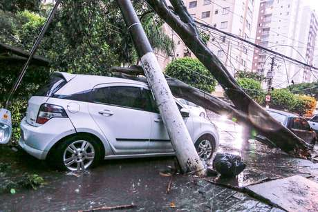 Um carro foi atingido por uma árvore, que também derrubou um poste, durante a forte chuva que atingiu a cidade de São Paulo.