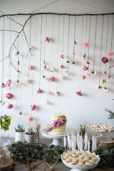 13. Decoração de chá de bebê com estilo rústico com folhagens na mesma e delicado painel com flores de papel ao fundo – Foto: Pinterest