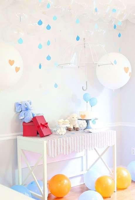 40. Decoração de chá de bebê bem clean com varal de gostas de chuva e bolas e guarda-chuva transparente – Foto: The Celebration Shoppe