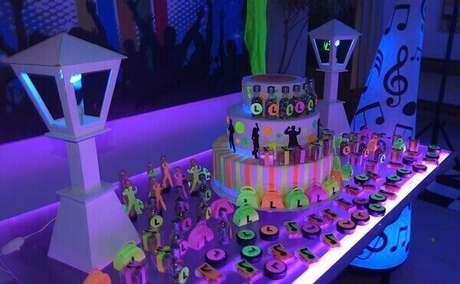 37. Em festa neon simples, o bolo e as lanternas laterais ganham destaque na mesa.