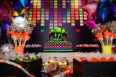 7. Painel colorido cria um cenário para mesa de doces e bolo em festa neon. Foto: Baladahall