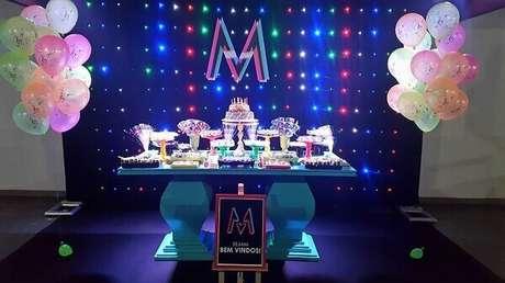 48. Painel feito com tecido atrás de mesa valorizam a decoração da festa neon. Foto: Guia Tudo Festa