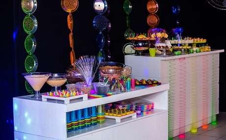 49. Mesas auxiliares ajudam na distribuição de doces e bebidas em festa neon. Foto: Pinterest