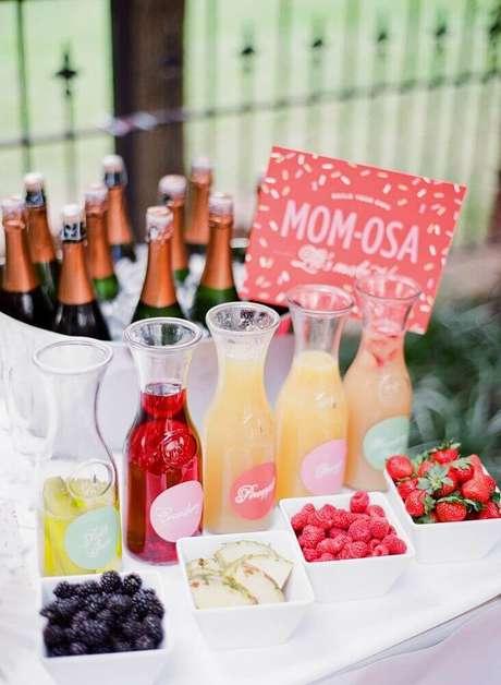 76. Uma mesa de bebidas e sucos fica bonita e criativa na decoração de chá de bebê, principalmente com frutas e champanhe – Foto: PartySlate