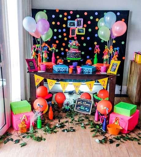 91. O móvel de madeira trouxe neutralidade para a decoração da festa neon. Fonte: Folia Eventos