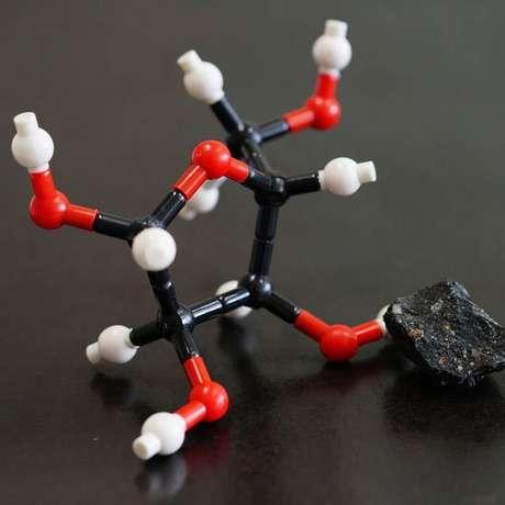 Um pedaço do meteorito Murchison ao lado do que seria a estrutura molecular da ribose, um dos açúcares encontrados em sua poeira