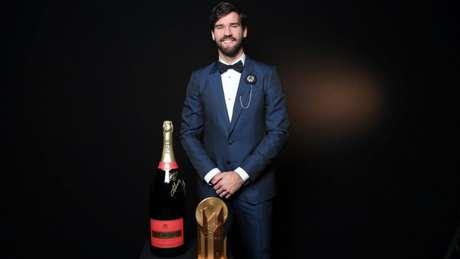 Alisson com o prêmio desta segunda (Foto: Divulgação / @francefootball)