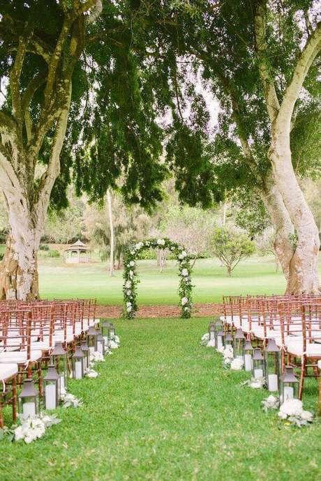 19. Decoração para cerimônia de casamento simples ao ar livre com arco de flores e lanternas de velas – Foto: Elizabeth Anne Designs