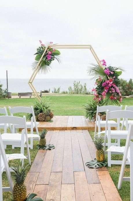 42. Decoração minimalista para cerimônia de casamento ao ar livre com arco moderno decorado com arranjo de flores – Foto: La Fleur