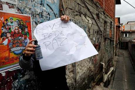 Morador de Paraisópolis segura cartaz pedindo paz
