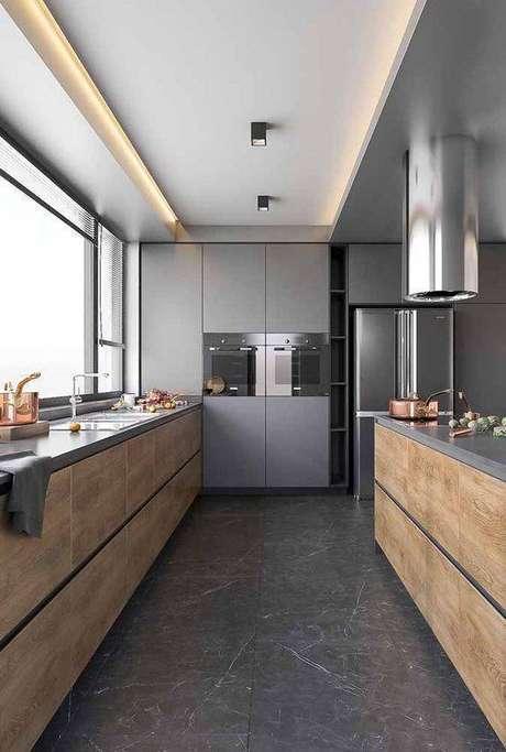 22. A cozinha cinza ganha muito com móveis de madeira crua. Foto: Ideias Decor