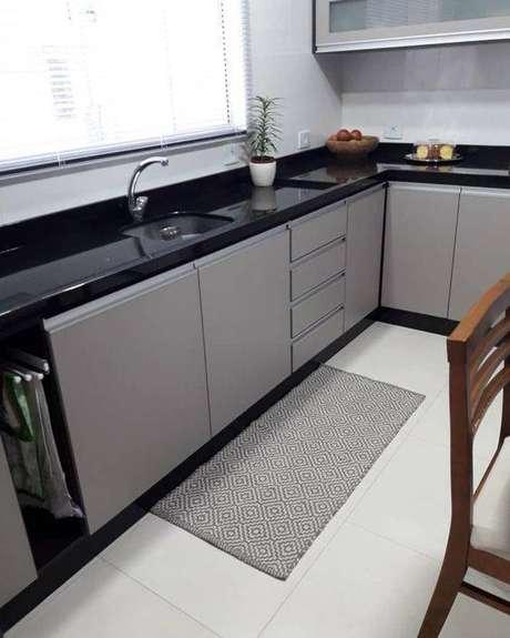 45. A bancada preta deixa a cozinha cinza mais moderna. Foto: Tua Casa