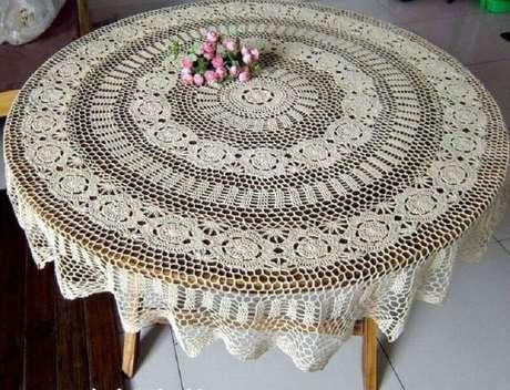 25. Mesa de madeira com toalha de mesa de crochê