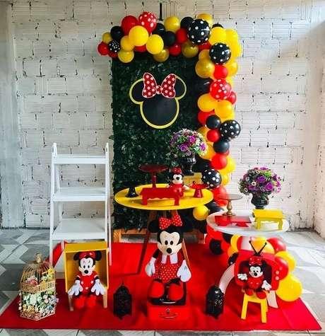 102 – Festa da Minnie simples com estante escada e painel com plantas artificiais. Fonte: Pinterest