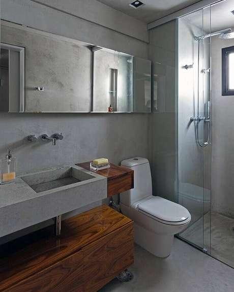 10. Banheiro moderno decorado com parede cinza de cimento queimado e armário de madeira – Foto: Diego Revollo