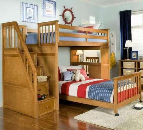 49. Nesse quarto decorado com beliche com escrivaninha de madeira também possui uma cama extra com rodinhas