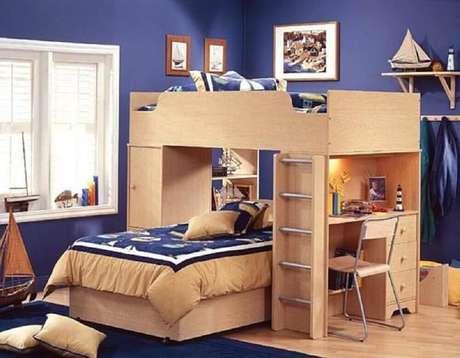 34. O beliche com escrivaninha de madeira ficou linda com as paredes do quarto azul